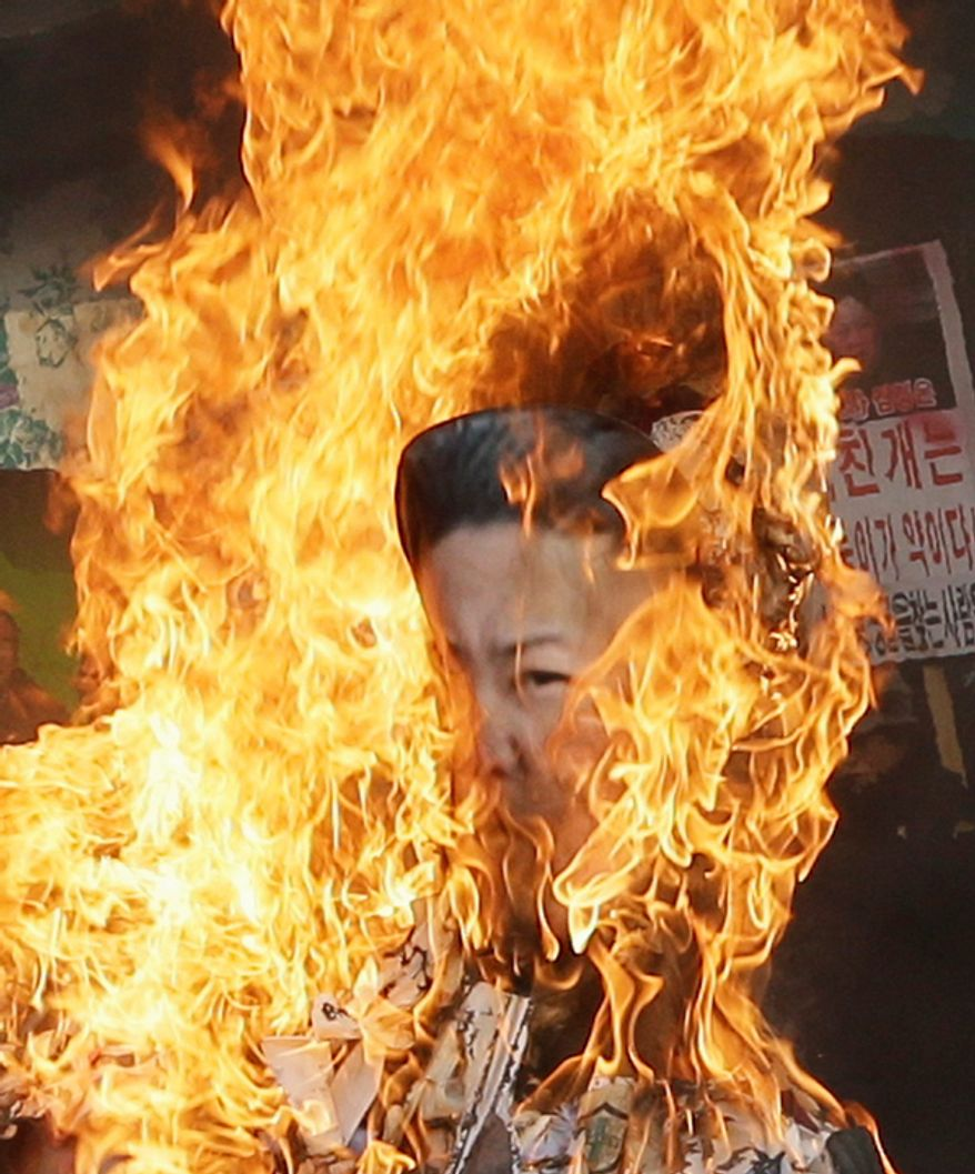 South Korean protesters burn an effigy of North Korean leader Kim Jong Un during a rally in Seoul on Dec. 13, 2012, denouncing North Korea's rocket launch. (Associated Press)