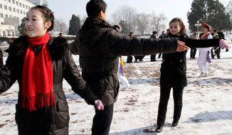 ** FILE ** North Korean youths dance before the Pyongyang Grand Theatre in Pyongyang, North Korea, to celebrate a rocket launch on Dec. 12, 2012. (Associated Press)