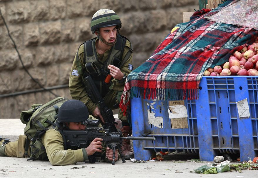 Israeli soldiers take aim during clashes with Palestinians (not seen) in the West Bank city of Hebron on Dec. 13, 2012, during the funeral of Mohammed Suleima, 17, who was killed by Israeli troops. Thousands of Palestinians marched through the streets of the city, chanting anti-Israel slogans and waving green Hamas flags. (Associated Press)