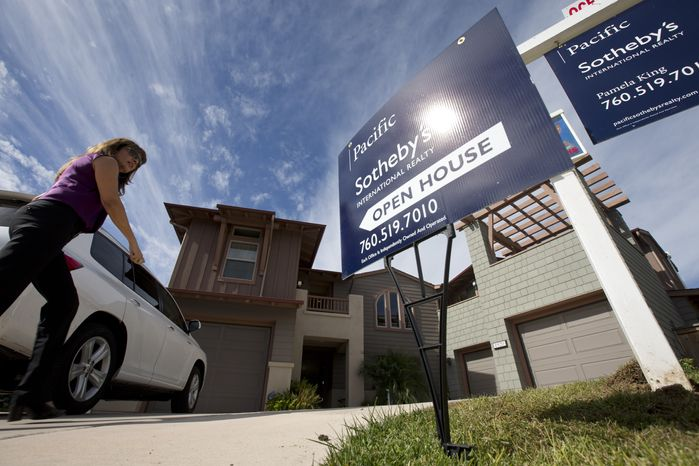**FILE** A woman walks towards a home for sale Nov. 14, 2012, during a viewing for brokers in Leucadia, Calif. (Associated Press)