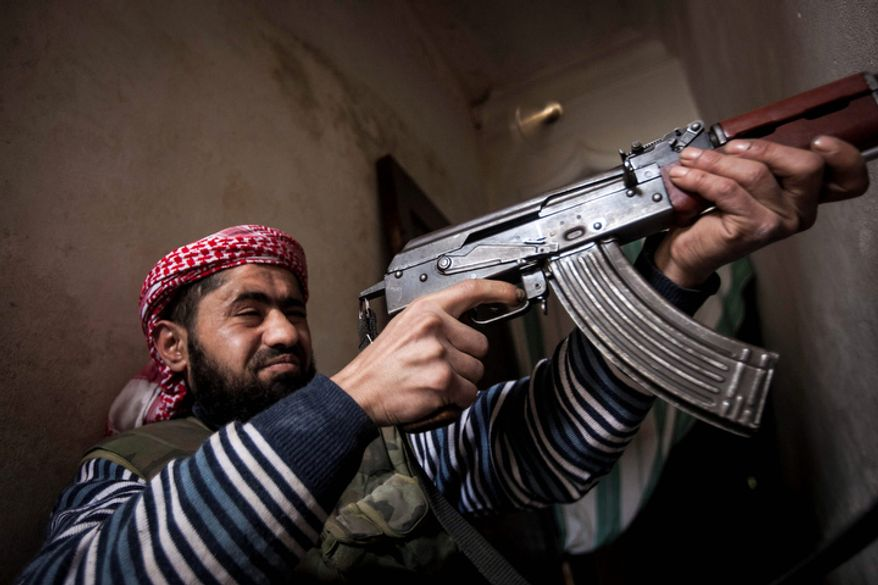 A Free Syrian Army fighter aims his weapon Dec. 10, 2012, during heavy clashes with government forces in Aleppo, Syria. (Associated Press)
