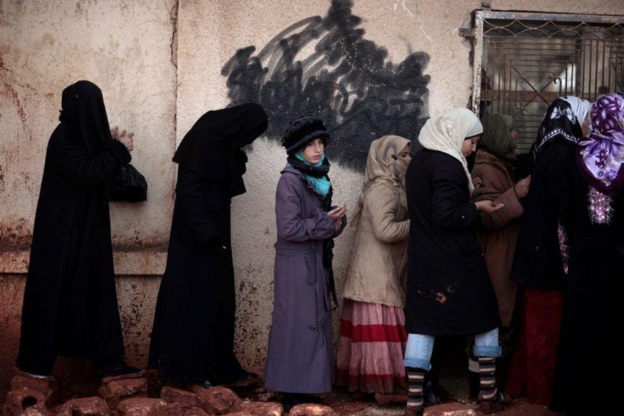 Syrian women wait outside a bakery shop to buy bread in Maaret Misreen, near Idlib, Syria, on Dec. 12, 2012. (Associated Press)