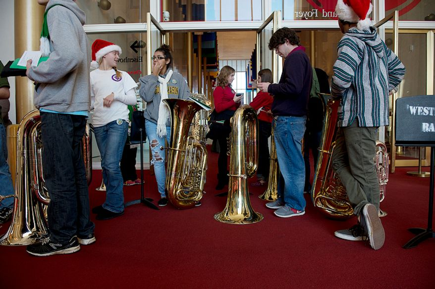 Students from Westfield High School in Centreville, Va., including (from left, Cathryn Kost, 16, Abigail Perez, 15, and Joseph Drzemiecki, 17, wait with their tubas in the Grand Foyer of the Kennedy Center for the start of the rehearsal for Tuba Christmas on Thursday, Dec. 13, 2012. Hundreds of tuba players came to the Kennedy Center Thursday to participate in Tuba Christmas, a concert that originated in 1974 as a tribute to the late artist/teacher William J. Bell, who was born on Christmas Day in 1902. Participants were asked to wear bright colors. They rehearsed for two hours before performing on the Millennium Stage at 6 p.m. (Barbara L. Salisbury/The Washington Times)