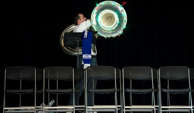 Tom Newman of Ashburn, Va. turns on the Christmas lights on his tuba before the start of the rehearsal for Tuba Christmas at the Millennium Stage at the Kennedy Center.  (Barbara L. Salisbury/The Washington Times)