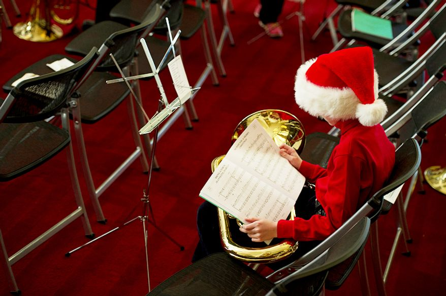 Aidan Smith, 11, of Bethesda, Md. looks over the music that he and hundreds of other tuba players will perform at the Millennium Stage at the Kennedy Center. (Barbara L. Salisbury/The Washington Times)