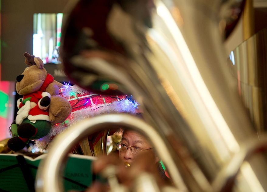 A tuba player is seen through another tuba while he rehearses with hundreds of other tubists at the Millennium Stage at the Kennedy Center in Washington, D.C. on Thursday, Dec. 13, 2012 for Tuba Christmas, an annual concert of tuba players. This is the 39th year for the concert, which started in Rockefeller Center in 1974. It is now held worldwide. (Barbara L. Salisbury/The Washington Times)