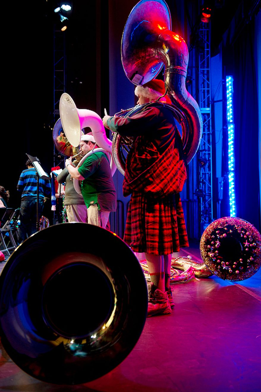 Bass tubists, including Santo Buzzanca, left, of Washington, D.C., rehearse on the Millennium Stage at the Kennedy Center in Washington, D.C. on Thursday, Dec. 13, 2012 for Tuba Christmas. More than 200 tubists participated in this year's event. (Barbara L. Salisbury/The Washington Times)