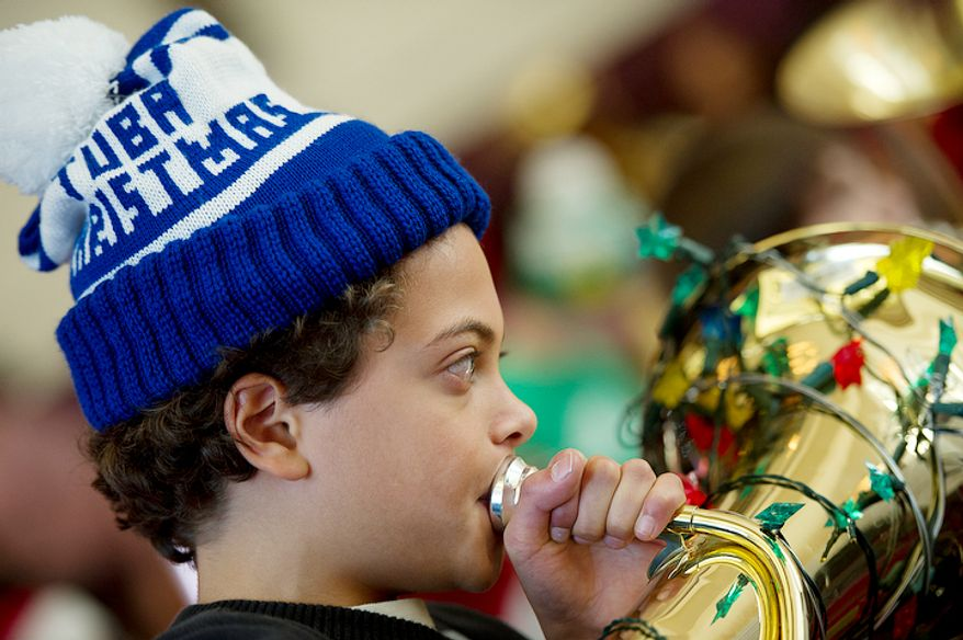 "Sporting his ""Tuba Christmas"" hat, Bryce Gaskins, 11, of Alexandria, Va. rehearses with hundreds of other tuba players forTuba Christmas, a concert that originated in 1974 as a tribute to the late artist/teacher William J. Bell, who was born on Christmas Day in 1902.  (Barbara L. Salisbury/The Washington Times)"