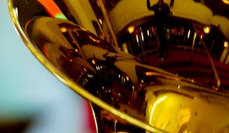 One of the conductors for Tuba Christmas 2012 is seen reflected in a tuba during rehearsal at the Kennedy Center's Millennium Stage. (Barbara L. Salisbury/The Washington Times)