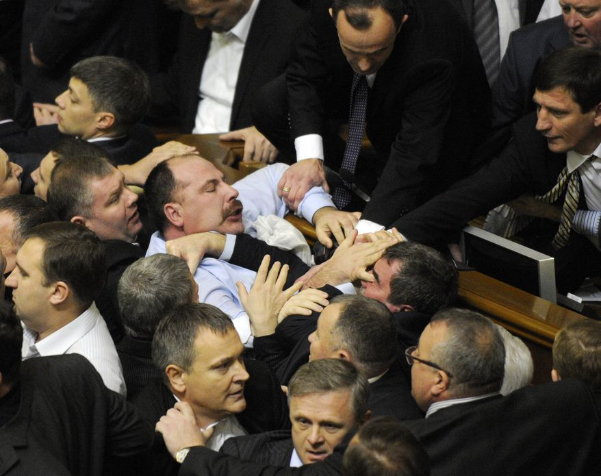 Ukrainian lawmakers fight around the rostrum during the first session of Ukraine's newly elected parliament in Kiev on Thursday, Dec. 13, 2012. (AP Photo/Sergei Chuzavkov)