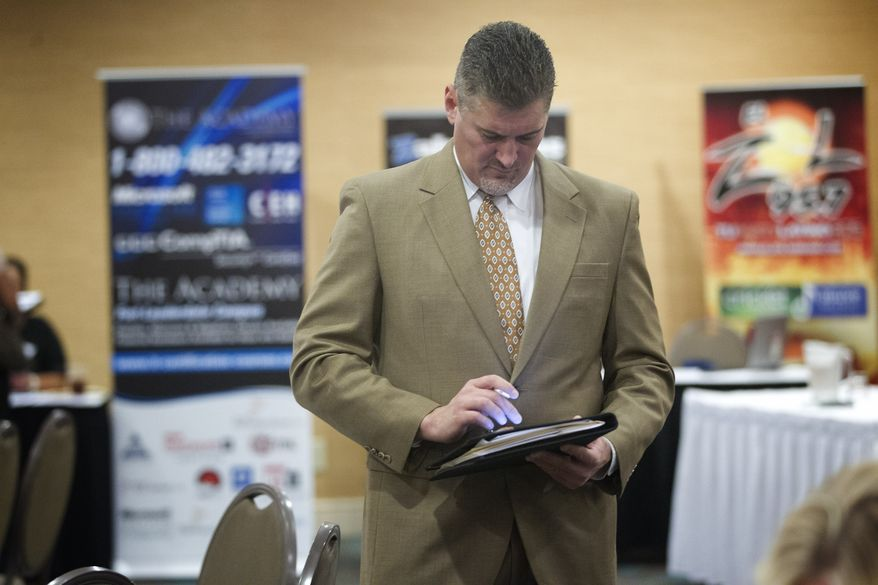 A job seeker uses his iPad to fill out job applications at the Fort Lauderdale Career Fair in Dania Beach, Fla., on Friday, Nov. 30, 2012. (AP Photo/J. Pat Carter)