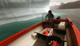 **FILE** A Greenlandic Inuit hunter and fisherman steers his boat past a melting iceberg, along a fjord leading away from the edge of the Greenland ice sheet, near Nuuk, Greenland, on July 26, 2011. (Associated Press)