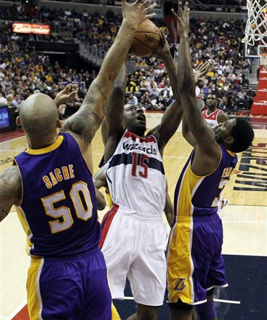 Washington Wizards guard Jordan Crawford (15) shoots between Los Angeles Lakers Robert Sacre (50) and forward Devin Ebanks (3) in the first half of an NBA basketball game Friday, Dec. 14, 2012 in Washington. The Lakers won 102-96. (AP Photo/Alex Brandon)