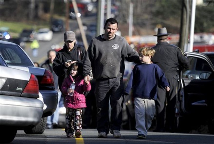 Parents leave a staging area after being reunited with their children following the shooting at the Sandy Hook Elementary School in Newtown, Conn., about 60 miles northeast of New York, on Friday, Dec. 14, 2012. Twenty schoolchildren and six staff members died in the rampage. (AP Photo/Jessica Hill)