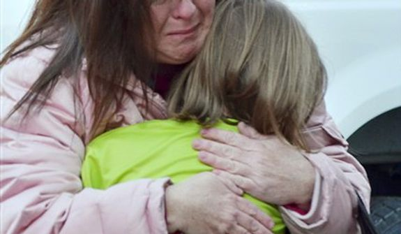 A mother hugs her daughter following the shootings at the Sandy Hook Elementary School in Newtown, Conn., about 60 miles northeast of New York City, on Friday, Dec. 14, 2012. (AP Photo/The New Haven Register, Melanie Stengel)