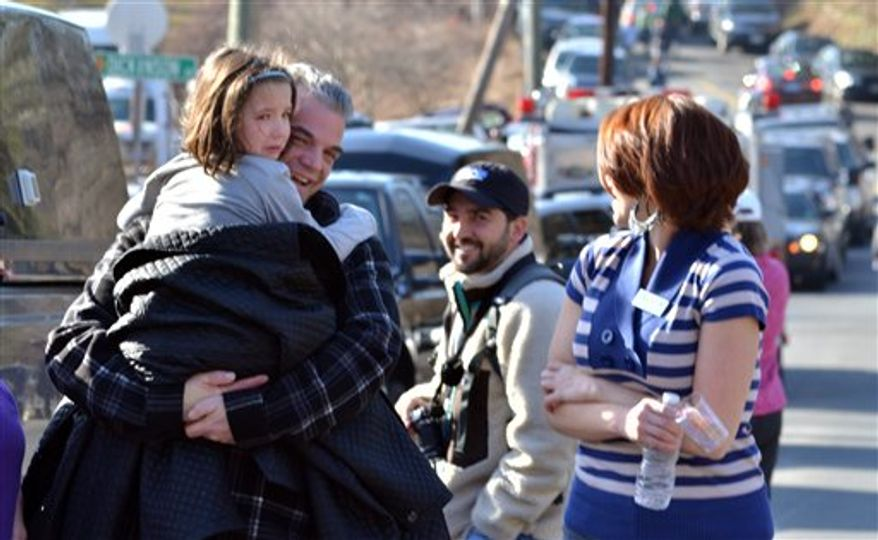A young girl is comforted following a shooting at the Sandy Hook Elementary School in Newtown, Conn., about 60 miles (96 kilometers) northeast of New York City, Friday, Dec. 14, 2012. An official with knowledge of Friday's shooting said 27 people were dead, including 18 children. It was the worst school shooting in the country's history. (AP Photo/The New Haven Register, Melanie Stengel)