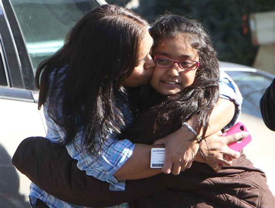 A woman hugs her daughter after being reunited at the Sandy Hook firehouse after a mass shooting at the Sandy Hook Elementary School in Newtown, Conn., on Friday, Dec. 14, 2012. (AP Photo/The Journal News, Frank Becerra Jr.)