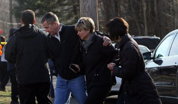 Teachers walk away from the Sandy Hook School following a shooting  at the school, Friday, Dec. 14, 2012 in Newtown, Conn. A man opened fire inside the Connecticut elementary school where his mother worked Friday, killing 26 people, including 18 children, and forcing students to cower in classrooms and then flee with the help of teachers and police. (AP Photo/The Journal News, Frank Becerra Jr.) MANDATORY CREDIT, NYC OUT, NO SALES, TV OUT, NEWSDAY OUT; MAGS OUT