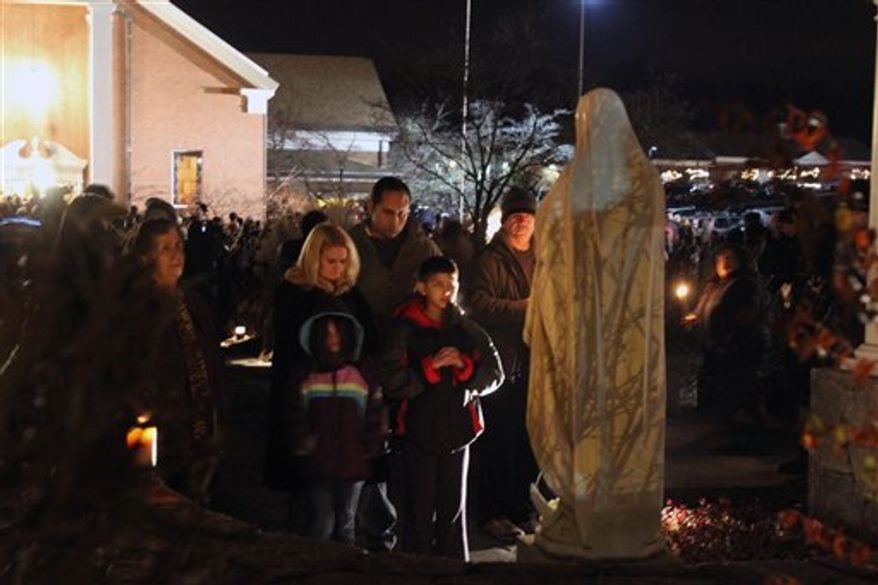 A family prays at a statue of the Virgin Mary outside Saint Rose of Lima church, Friday, Dec. 14, 2012 in Newtown, Conn. A man killed his mother at home and then opened fire Friday inside the elementary school where she taught, massacring 26 people, including 20 children, as youngsters cowered in fear to the sound of gunshots echoing through the building and screams coming over the intercom. (AP Photo/The Journal News, Frank Becerra Jr.
