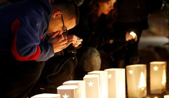 A man reacts placing candles on a makeshift memorial in honor of the victims who died a day earlier when a gunman opened fire in an elementary school, Saturday, Dec. 15, 2012, in Newtown, Conn. The man, who died from a self-inflicted wound, allegedly killed his mother at their home and then opened fire Friday inside the Sandy Hook Elementary school, massacring 26 people, including 20 children. (AP Photo/Julio Cortez)