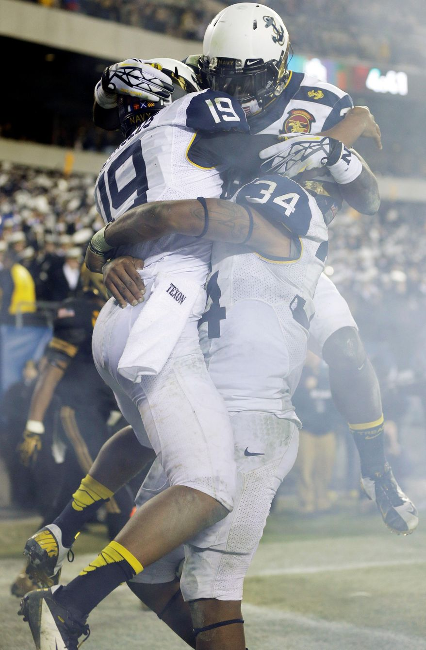Navy's Keenan Reynolds (19) celebrates a touchdown with Noah Copeland (34) and Gee Gee Greene, top, during the second half of an NCAA college football game against Army, Saturday, Dec. 8, 2012, in Philadelphia. Navy won 17-13. (AP Photo/Matt Rourke)