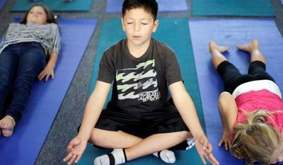 Fourth-grader Miguel Ruvalcaba holds a pose during a yoga class at Capri Elementary School in Encinitas, Calif. Officials of the school district are treading softly as they pioneer what may be the first district-wide yoga program of its kind, while also trying to avoid a legal dispute about religion. (Associated Press)