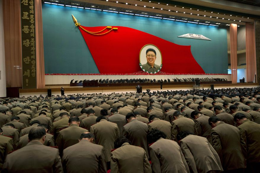 """** FILE ** North Korean military officers bow at an image of the late North Korean leader Kim Jong-il during a national meeting of top party and military officials on the eve of the first anniversary of Kim's death in Pyongyang, North Korea, on Sunday, Dec. 16, 2012. The large characters on the vertical banner at left translate as """"Hurrah to the Workers' Party of Korea."""" (AP Photo/Ng Han Guan)"""