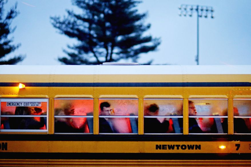 People arrive on a school bus at Newtown High School for a memorial vigil attended by President Barack Obama for the victims of the Sandy Hook Elementary School shooting, Sunday, Dec. 16, 2012, in Newtown, Conn. (AP Photo/David Goldman)