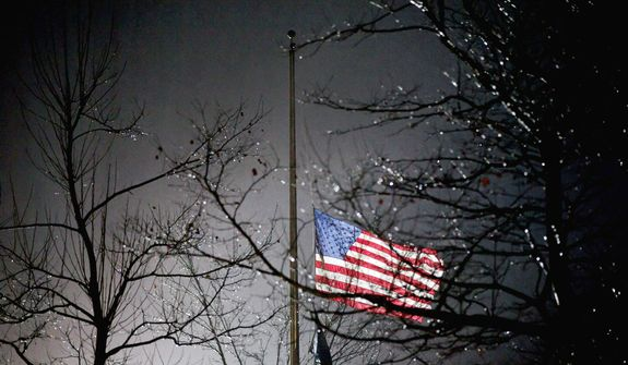 A U.S. flag flies at half staff outside the  Newtown High School before President Barack Obama is scheduled to attend a memorial for the victims of the Sandy Hook Elementary School shooting, Sunday, Dec. 16, 2012, in Newtown, Conn.(AP Photo/David Goldman)