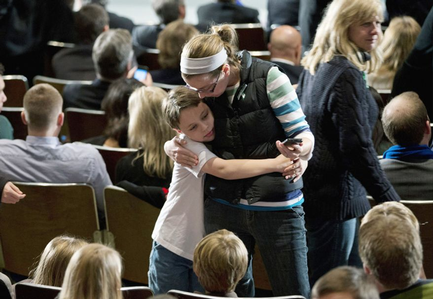 Residents greet each other before the start of an interfaith vigil for the victims of the Sandy Hook Elementary School shooting on Sunday, Dec. 16, 2012 at Newtown High School in Newtown, Conn.    (AP Photo/ Evan Vucci)