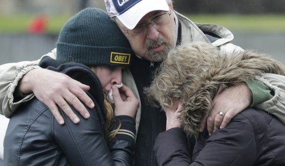 A man clutches two sobbing women at the site of a makeshift memorial for school shooting victims at the village of Sandy Hook in Newtown, Conn., on Sunday, Dec. 16, 2012. A gunman opened fire at the Sandy Hook Elementary School, killing 26 people, including 20 children, before killing himself on Friday. (AP Photo/Charles Krupa)