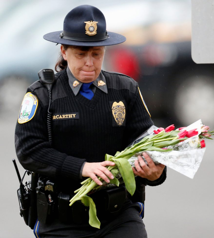 Newtown Police Officer Maryhelen McCarthy places flowers at a makeshift memorial outside St. Rose of Lima Roman Catholic Church, Sunday, Dec. 16, 2012, in Newtown, Conn. (AP Photo/Julio Cortez)