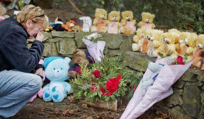 Cheryl Girardi, of Middletown, Conn., kneels beside 26 teddy bears, each representing a victim of the Sandy Hook Elementary School shooting, at a sidewalk memorial, Sunday, Dec. 16, 2012, in Newtown, Conn. (AP Photo/David Goldman)