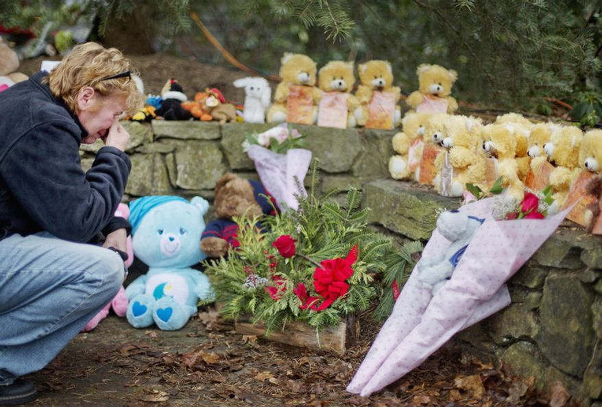 Cheryl Girardi, of Middletown, Conn., kneels beside 26 teddy bears, each representing a victim of the Sandy Hook Elementary School shooting, at a sidewalk memorial, Sunday, Dec. 16, 2012, in Newtown, Conn. (AP Photo/David Goldman)