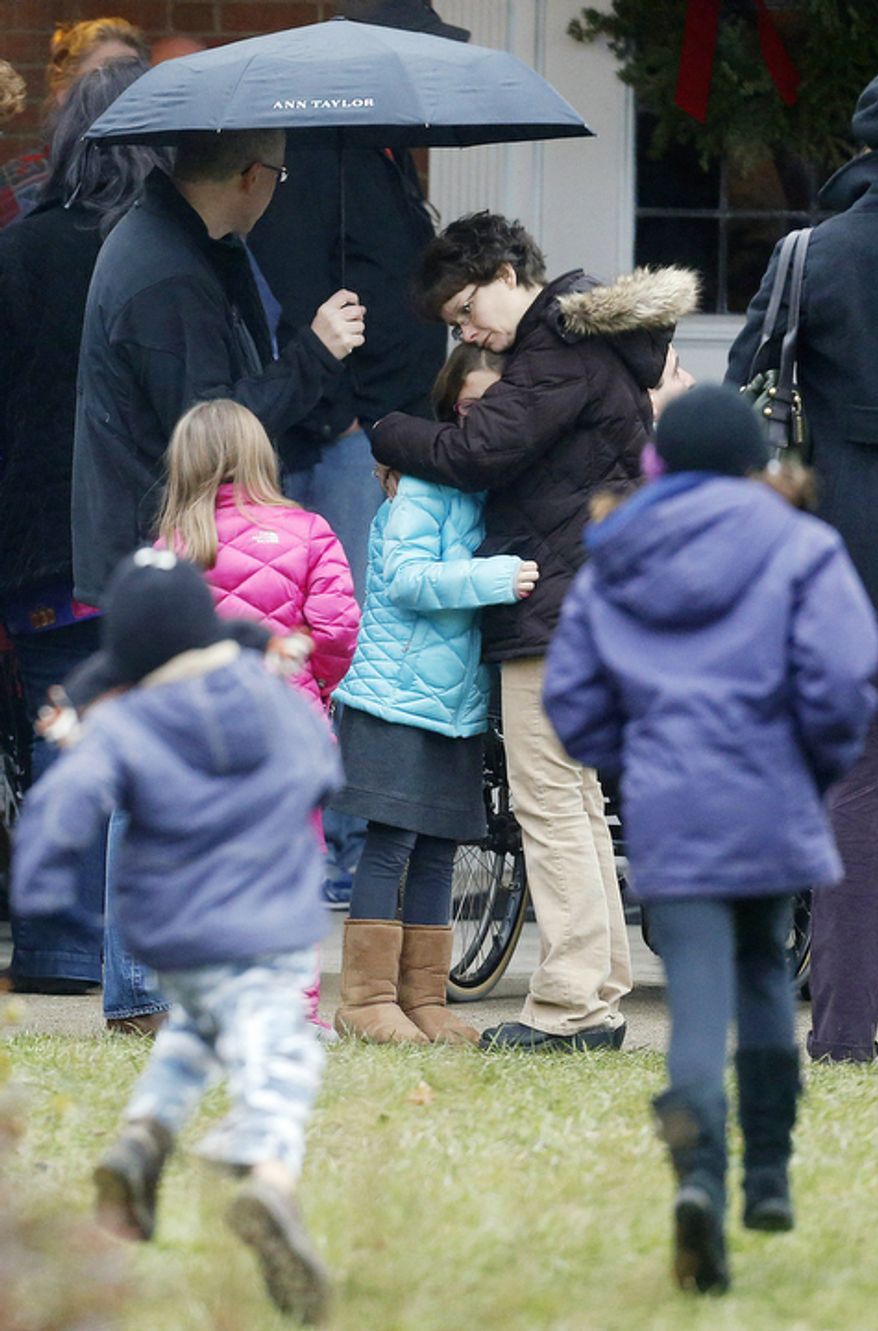 A woman embraces a child as children run outside of St. Rose of Lima Roman Catholic Church before a Sunday mass service, Sunday, Dec. 16, 2012, in Newtown, Conn. (AP Photo/Julio Cortez)