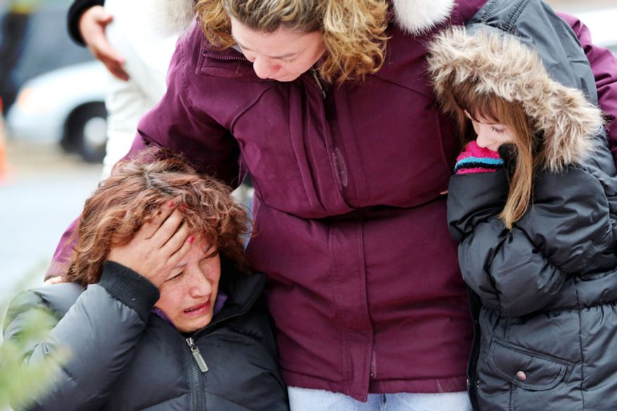 Mourners grieve at one of the makeshift memorials for victims of the Sandy Hook Elementary School shooting, Sunday, Dec. 16, 2012, in Newtown, Conn.  (AP Photo/Mary Altaffer)