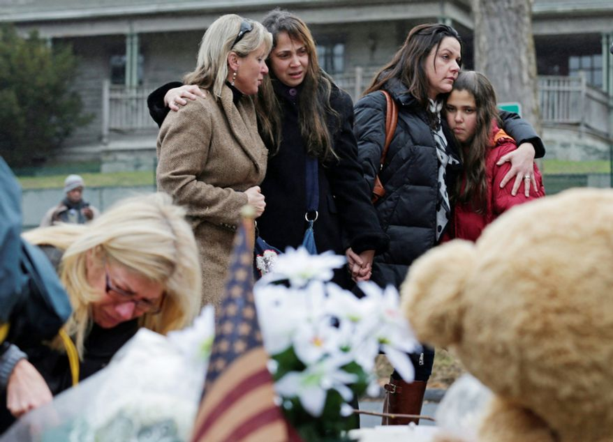 Women embrace at the site of a makeshift memorial for school shooting victims at the village of Sandy Hook in Newtown, Conn., Sunday, Dec. 16, 2012.  (AP Photo/Charles Krupa)