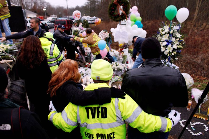 Onlookers embrace as firefighters and other volunteers reorganize a memorial for shooting victims near Sandy Hook Elementary School before erecting a shelter over it, Sunday, Dec. 16, 2012 in Newtown, Conn. (AP Photo/Jason DeCrow)