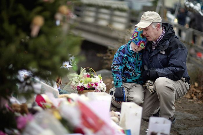 David Freedman, right, kneels with his son Zachary, 9, both of Newtown, Conn., as they visit a sidewalk memorial for the Sandy Hook Elementary School shooting victims, Sunday, Dec. 16, 2012, in Newtown, Conn. (AP Photo/David Goldman)