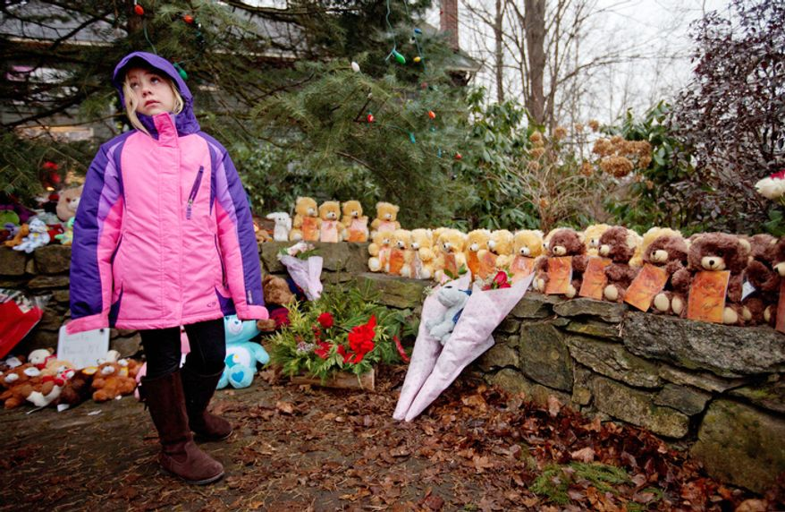 Ava Staiti, 7, of New Milford, Conn., looks up at her mother Emily Staiti, not pictured, while visiting a sidewalk memorial with 26 teddy bears, each representing a victim of the Sandy Hook Elementary School shooting, Sunday, Dec. 16, 2012, in Newtown, Conn.  (AP Photo/David Goldman)