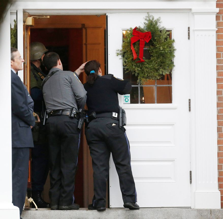Newtown Police Officer Maryhelen McCarthy, right, looks into St. Rose of Lima Roman Catholic Church with other officials while responding to a threat, Sunday, Dec. 16, 2012, in Newtown, Conn. Worshippers hurriedly left the church on Sunday, saying they were told there was a bomb threat, not far from the elementary school where 20 kids and six adults were massacred on Friday. The all-clear was given after an hour in which armed police in SWAT gear searched the church and adjacent buildings. (AP Photo/Julio Cortez)