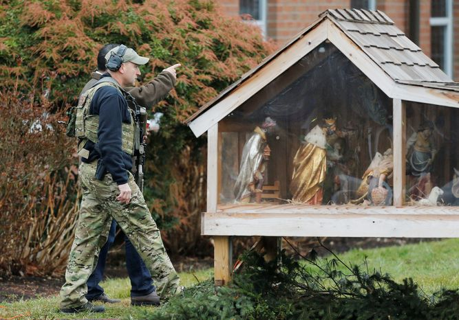 A Connecticut State Police tactical team searches the area around St. Rose of Lima Catholic Church while responding to a bomb threat, Sunday, Dec. 16, 2012, in Newtown, Conn. Worshippers hurriedly left the church Sunday, not far from where a gunman opened fire Friday inside the Sandy Hook Elementary School in Newtown. (AP Photo/Charles Krupa)