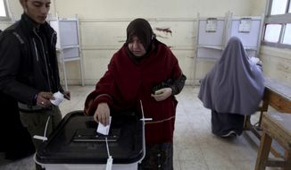 An Egyptian woman casts her vote in Cairo on Saturday, Dec. 15, 2012, during a referendum on a disputed constitution drafted by Islamist supporters of President Mohammed Morsi. (AP Photo/Khalil Hamra)