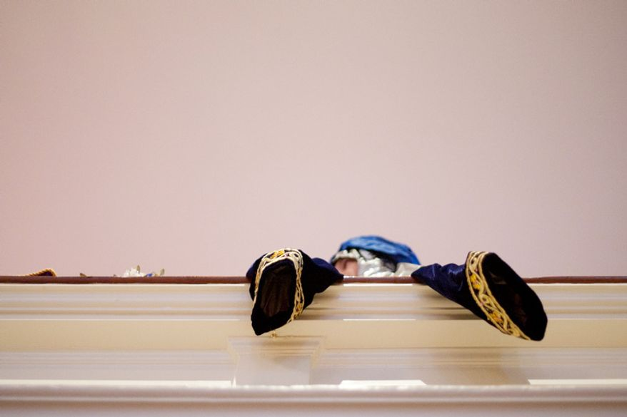 A Christ Church Sunday school and youth group participant dangles her costume over the balcony as she waits for her part during the Christmas Pageant in Alexandria, Va., on Sunday, December 16, 2012.  (Craig Bisacre/The Washington Times)
