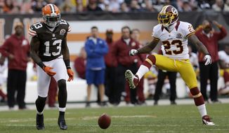 Cleveland Browns wide receiver Josh Gordon can't get to the ball under defense from Washington Redskins cornerback DeAngelo Hall (23) during an NFL football game Sunday, Dec. 16, 2012, in Cleveland. (AP Photo/Tony Dejak)