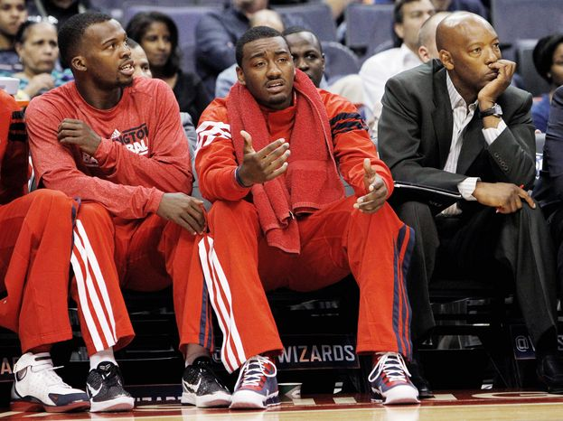 Wizards point guard John Wall (center) has yet to play this season after suffering a stress injury to his left knee just before the start of training camp. Washington is an NBA-worst 3-18 entering Tuesday's home against Atlanta. (Associated Press)