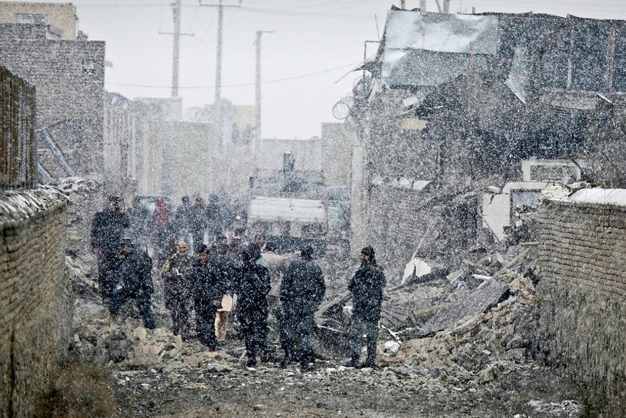 Afghan security men inspect the scene of a car bomb explosion in Kabul, Afghanistan, on Monday, Dec. 17, 2012. The bomb exploded outside of a compound housing a U.S. military contractor in the Afghan capital, blowing apart an exterior wall and wounding dozens inside, company representatives and police said. (AP Photo/Musadeq Sadeq)