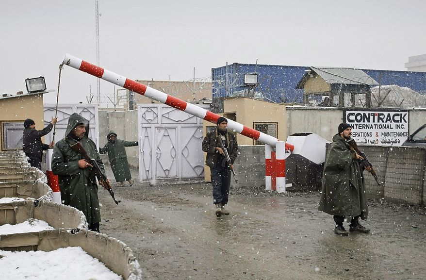 Afghan security members of the Contrack company stand guard following a car bomb explosion in Kabul, Afghanistan, on Monday, Dec. 17, 2012. The bomb exploded outside of a compound housing a U.S. military contractor in the Afghan capital, blowing apart an exterior wall and wounding dozens inside, company representatives and police said. (AP Photo/Musadeq Sadeq)