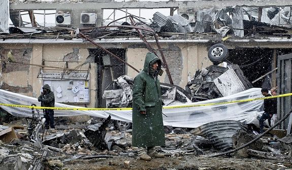 An Afghan security member stands at the scene of a car bomb explosion in Kabul, Afghanistan, on Monday, Dec. 17, 2012. The bomb exploded outside of a compound housing a U.S. military contractor in the Afghan capital, blowing apart an exterior wall and wounding dozens inside, company representatives and police said. In another part of the country, a suspected landmine killed several young girls, police said. (AP Photo/Musadeq Sadeq)