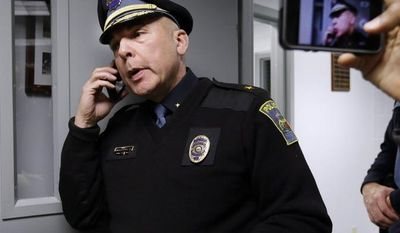 Kingston, N.H. Police Chief Donald Briggs Jr. speaks on his cellphone and relays information to members of the media at police headquarters in Kingston, N.H., Saturday, Dec. 15, 2012, as he talks with part-time Kingston Police Officer James Champion, brother of slain Nancy Lanza. (AP Photo/Elise Amendola)